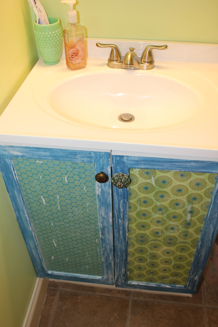 BORING BATHROOM HACK! Do your cabinet doors need a facelift, but you are unsure where to start? Well, embrace your inner Pinner, and take a look at this darling idea my mom and I came up with. All you need is paint, scrapbook paper (wrapping paper could also work), decoupauge glue (we used Modge Podge), and knobs to change out! TAH DAH! Say buh-bye to your boring bathroom cabinet doors and hello to FRESH and BOLD ones :)
